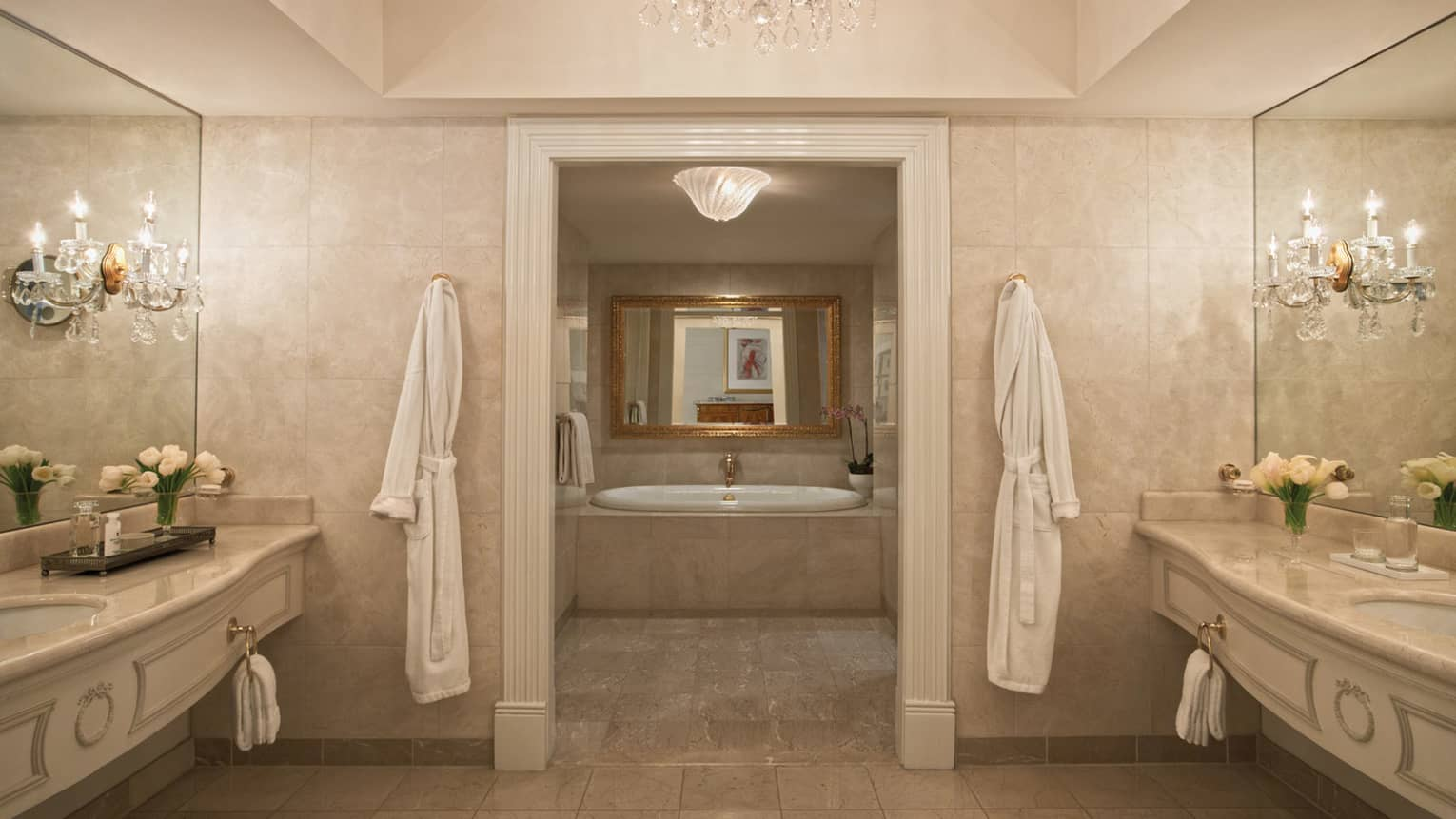 Presidential Suite master marble bathroom with white robes hanging on either side of doorway to tub
