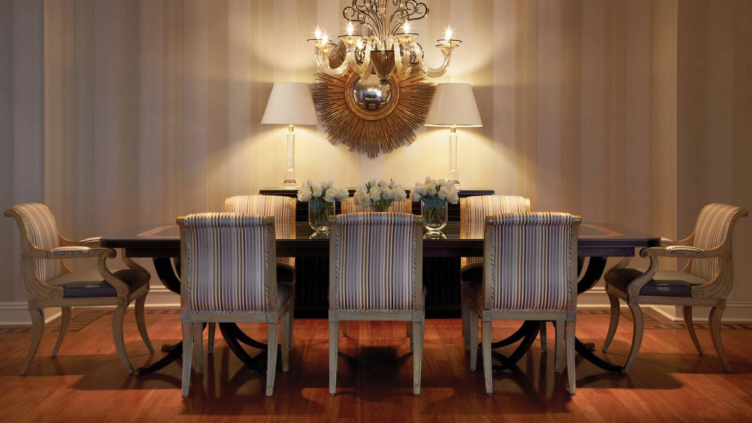 Presidential Suite private dining table with striped chairs, white flowers, chandelier, gold art
