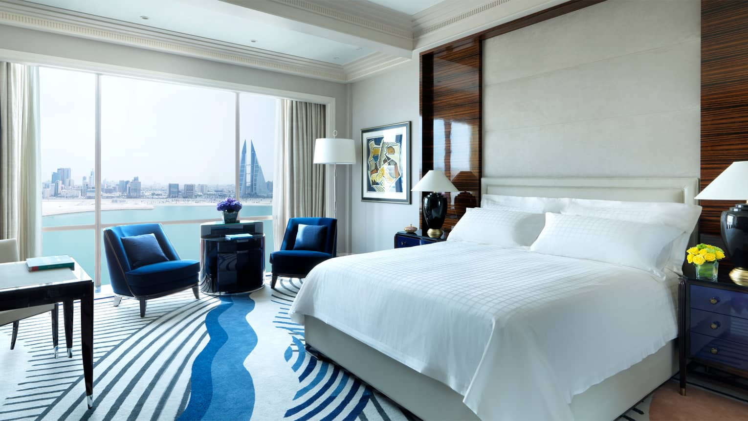Deluxe Room bed, modern blue-and-white carpet, two blue armchairs in front of sunny windows