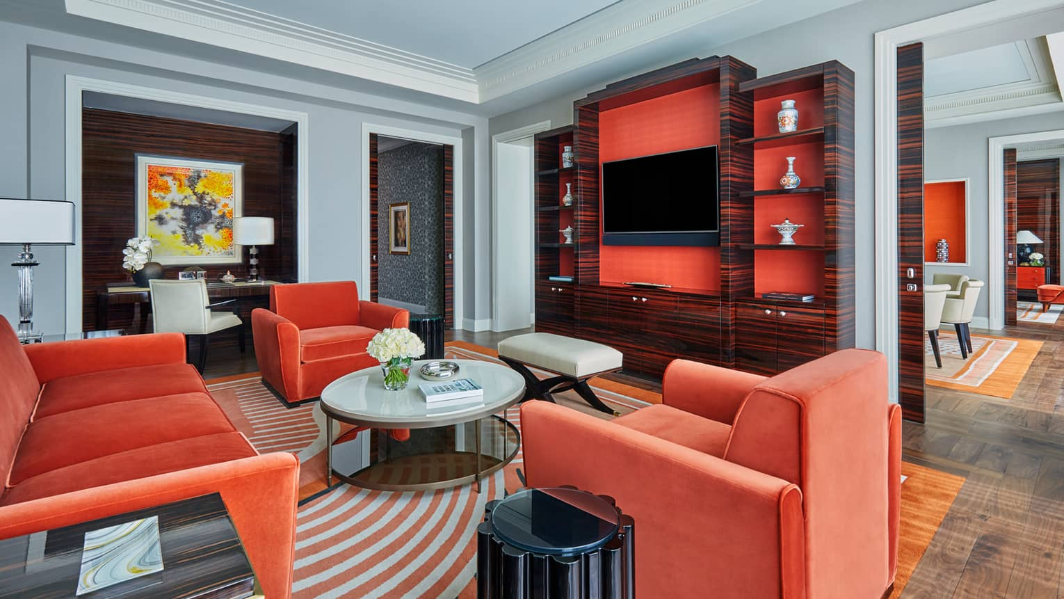 State Suite with warm orange velvet sofa and chairs, round coffee table, TV cabinet