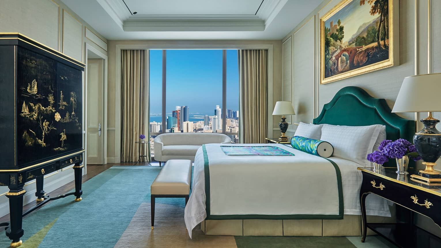 Presidential Suite side view of bed, bench at foot, decorative black dresser, window with city view