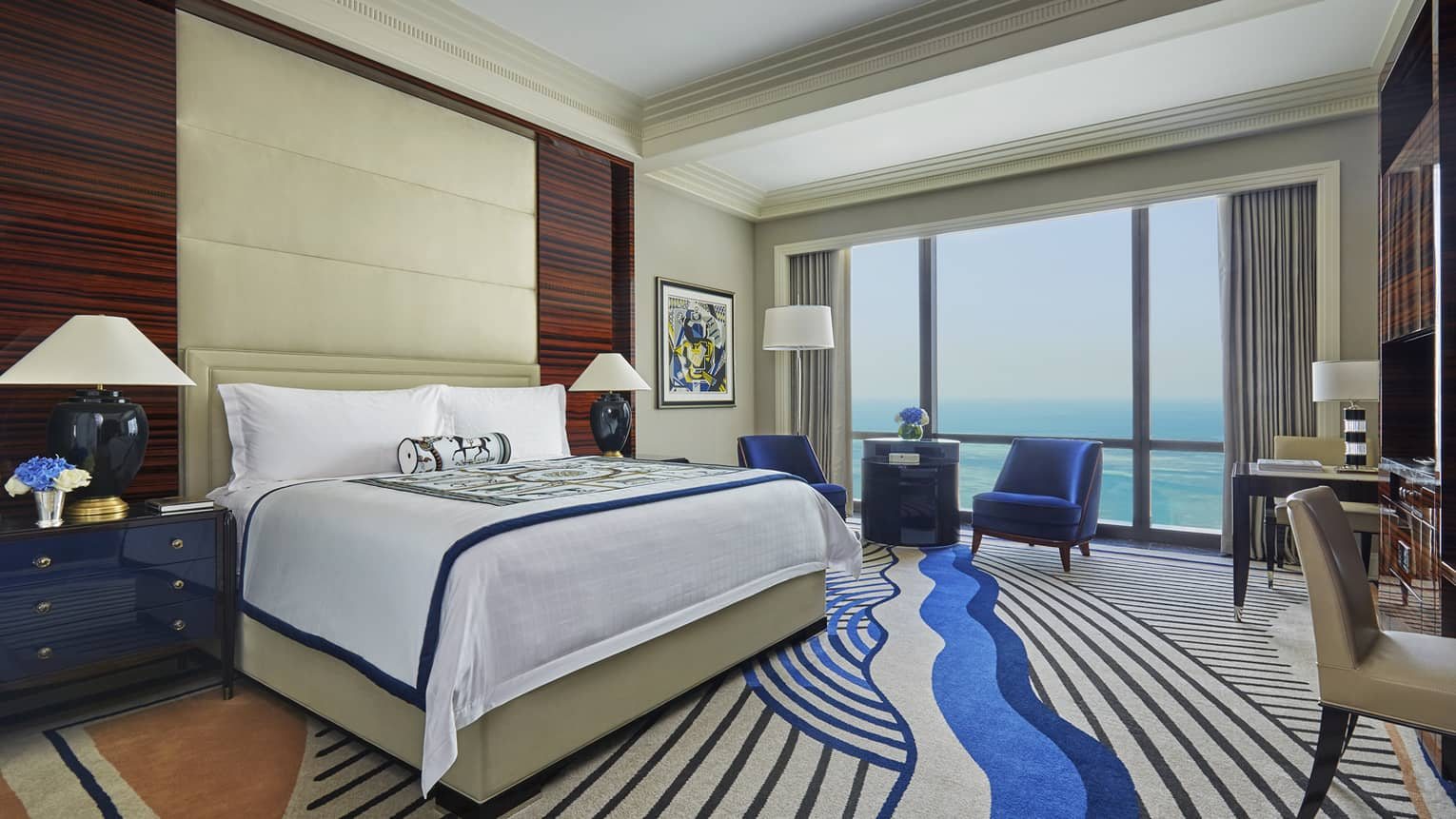 Premier Room bed with tall padded headboard, modern carpet with blue swirl design, floor-to-ceiling window with Arabian Gulf view