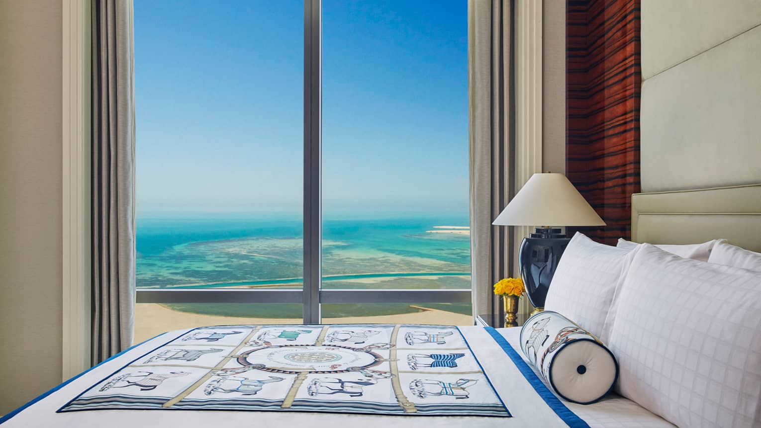 Premier Room top side view of bed with decorative blanket in front of floor-to-ceiling window with Arabian Gulf view