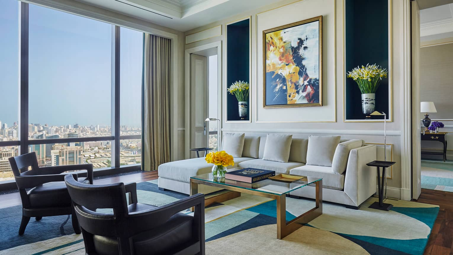 Hotel room living area with L-shaped white sofa, two small armchairs, coffee table with books, colourful painting, flowers