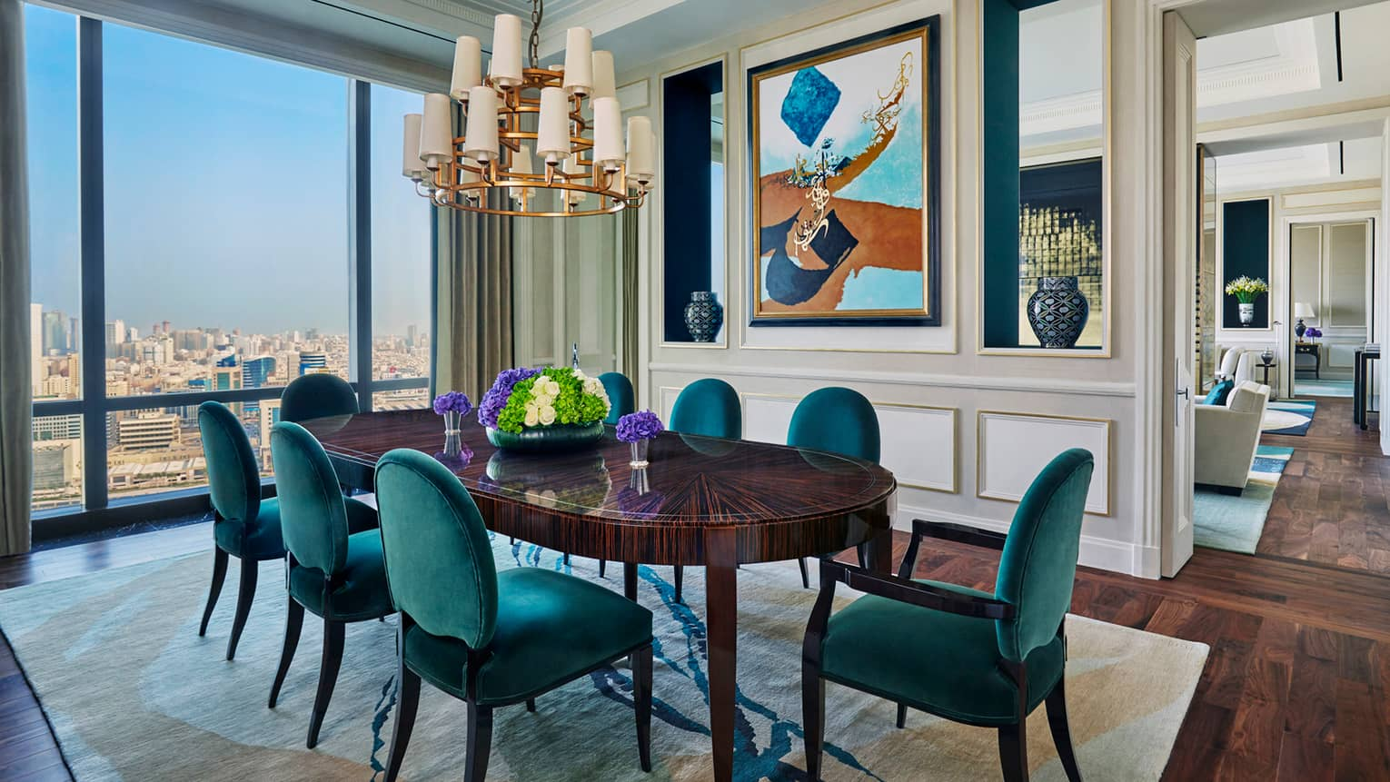 Hotel room 1930s-style 8-person dining room table with maritime green velvet chairs, chandelier, window with city view