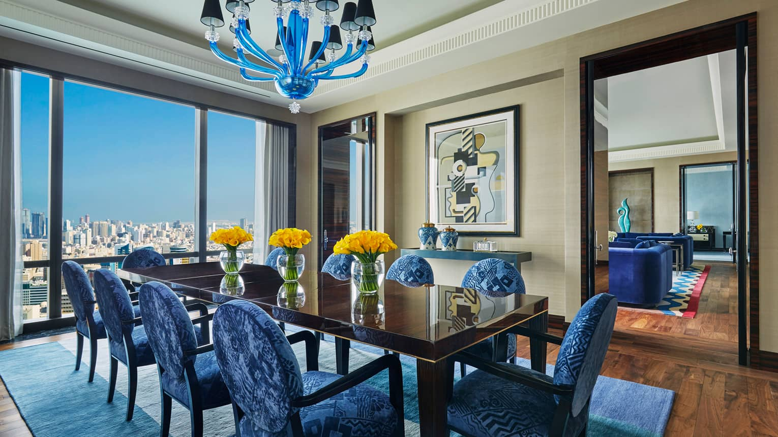 Royal Suite 10-person dining table with modern blue patterned chairs, vases of yellow flowers, blue pendant chandelier