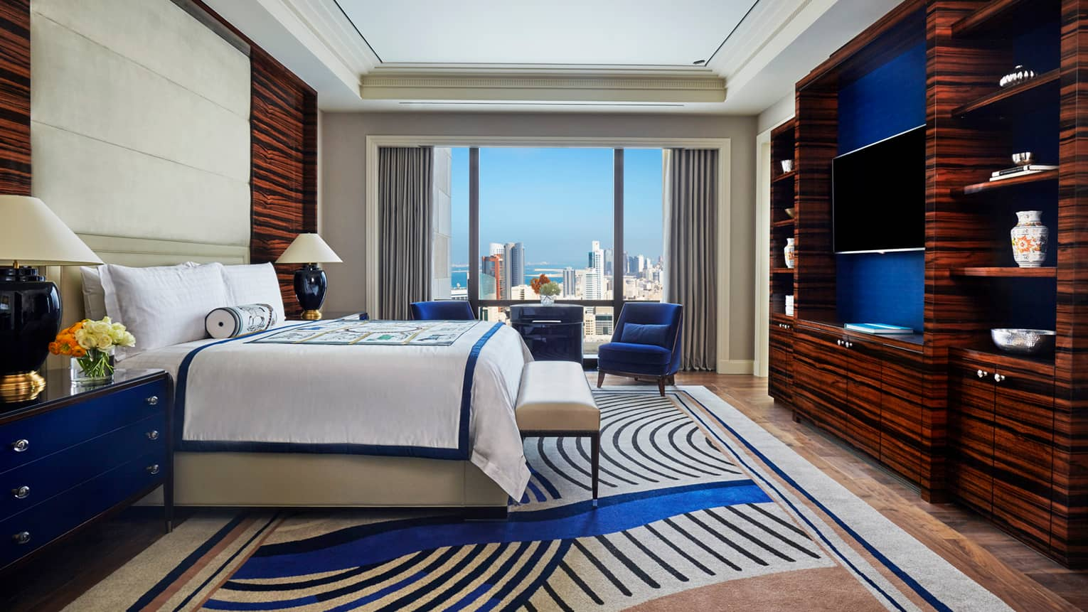 Superior Room side view of bed with decorative blanket and rolled pillow, modern blue carpet, armchair by window