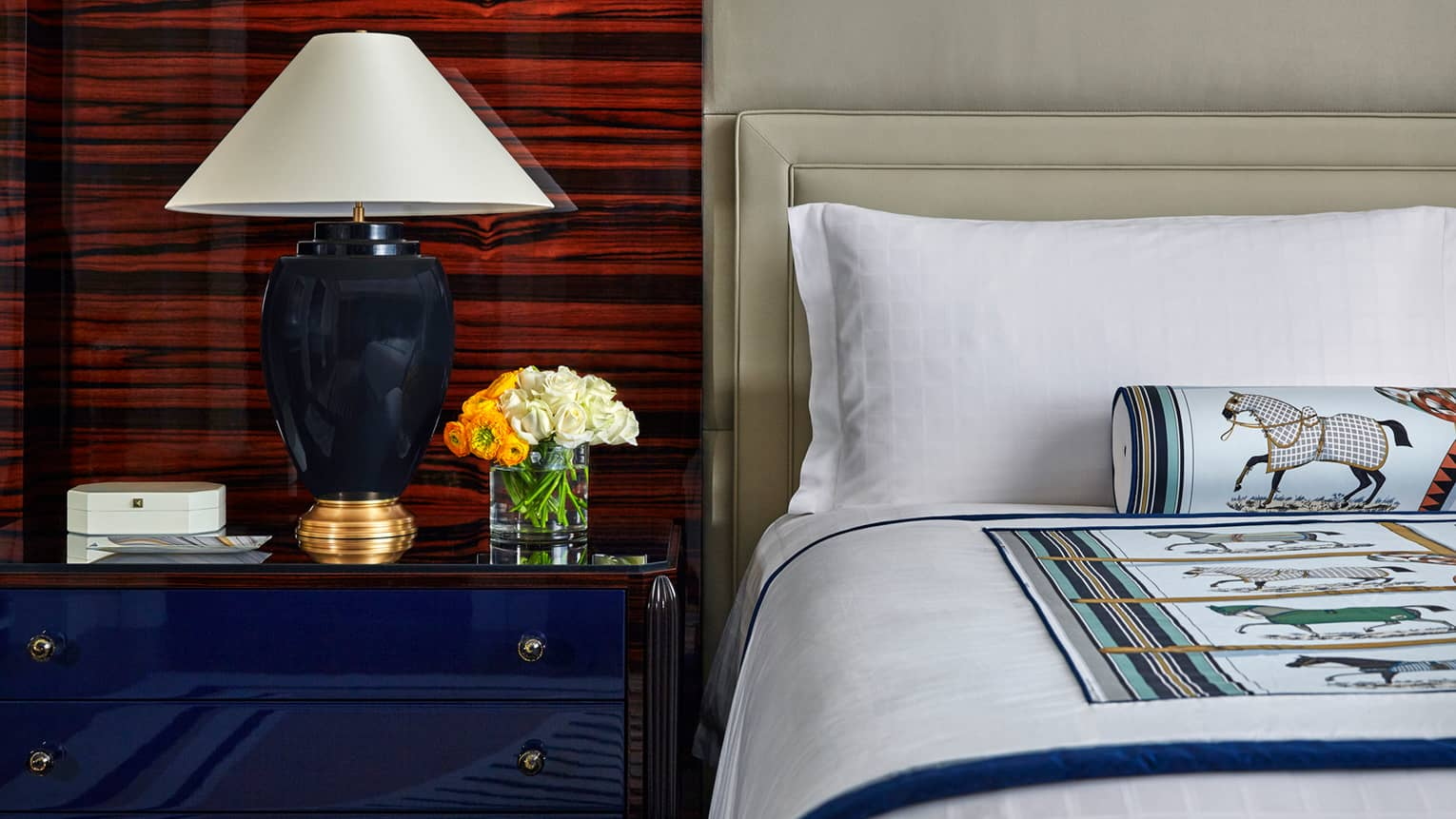 Superior Room close-up of corner of bed, pillow, decorative horse on rolled accent pillow, blue nightstand