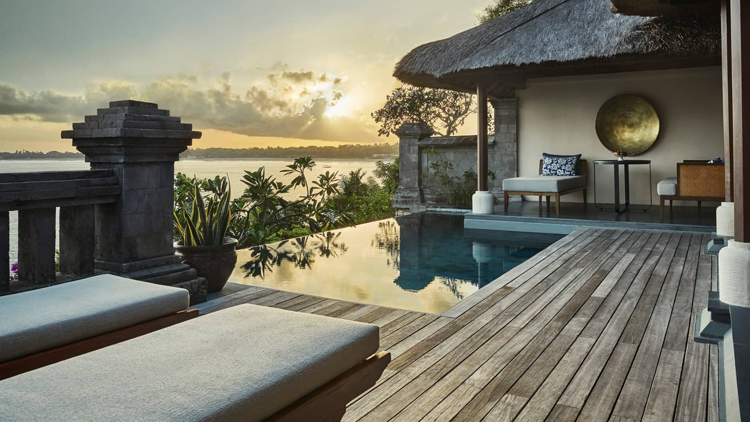Ocean sunset reflecting on private villa swimming pool, palm trees, thatched roof, lounge chairs
