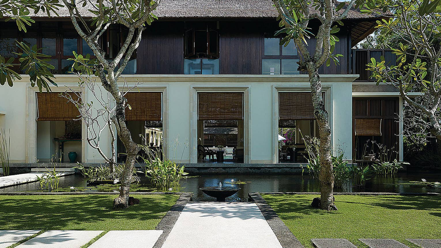 Exterior villa view with pond, small fountain, manicured green lawn, tropical trees
