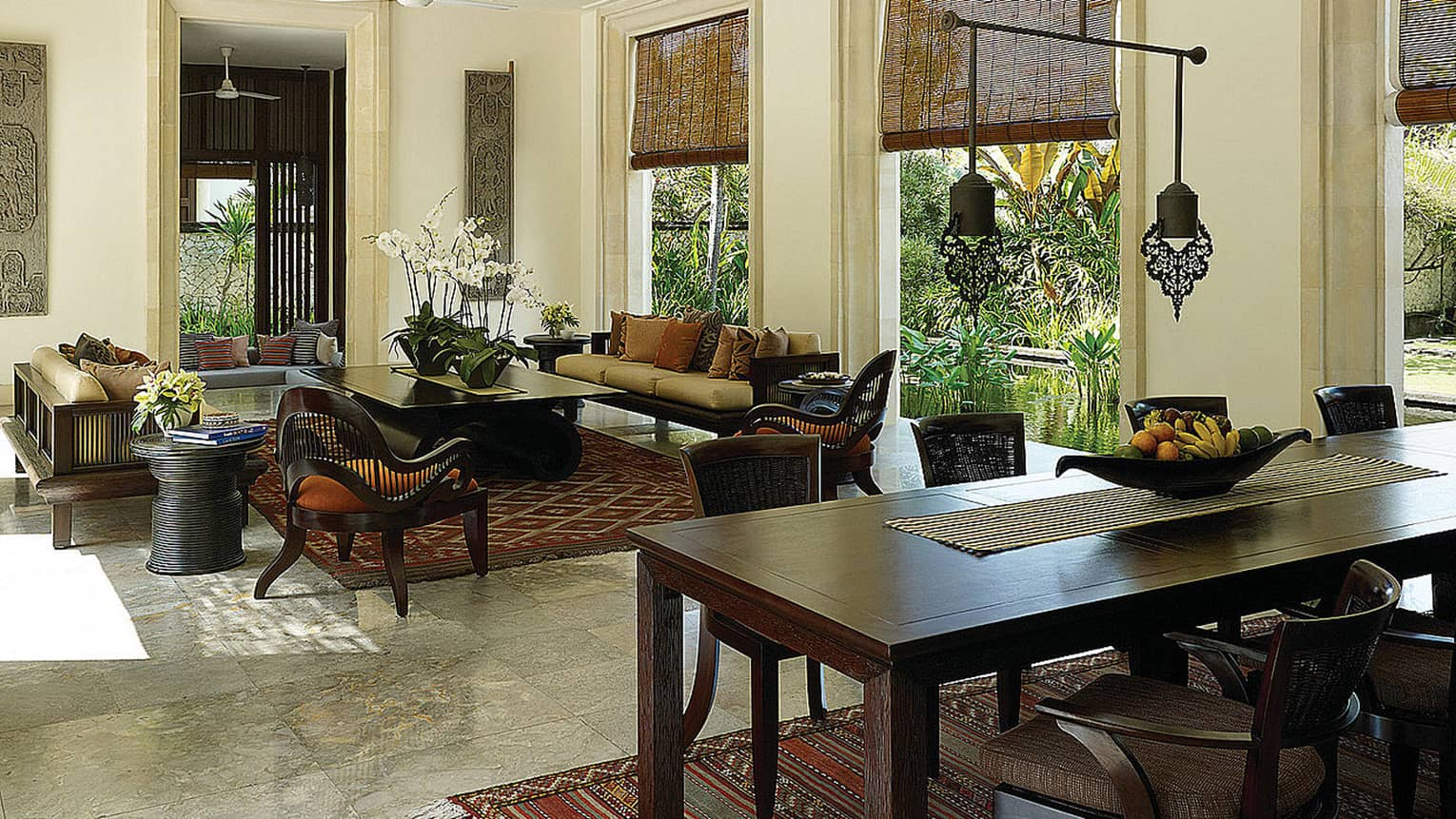 Large wood dining table near living area, Balinese textile rugs, windows overlooking tropical garden