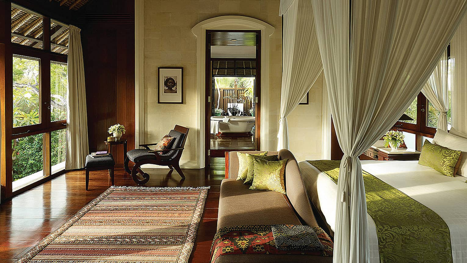 Sunlight coming in bedroom over Balinese rug, small chaise at foot of bed with velvet green sash, white curtains