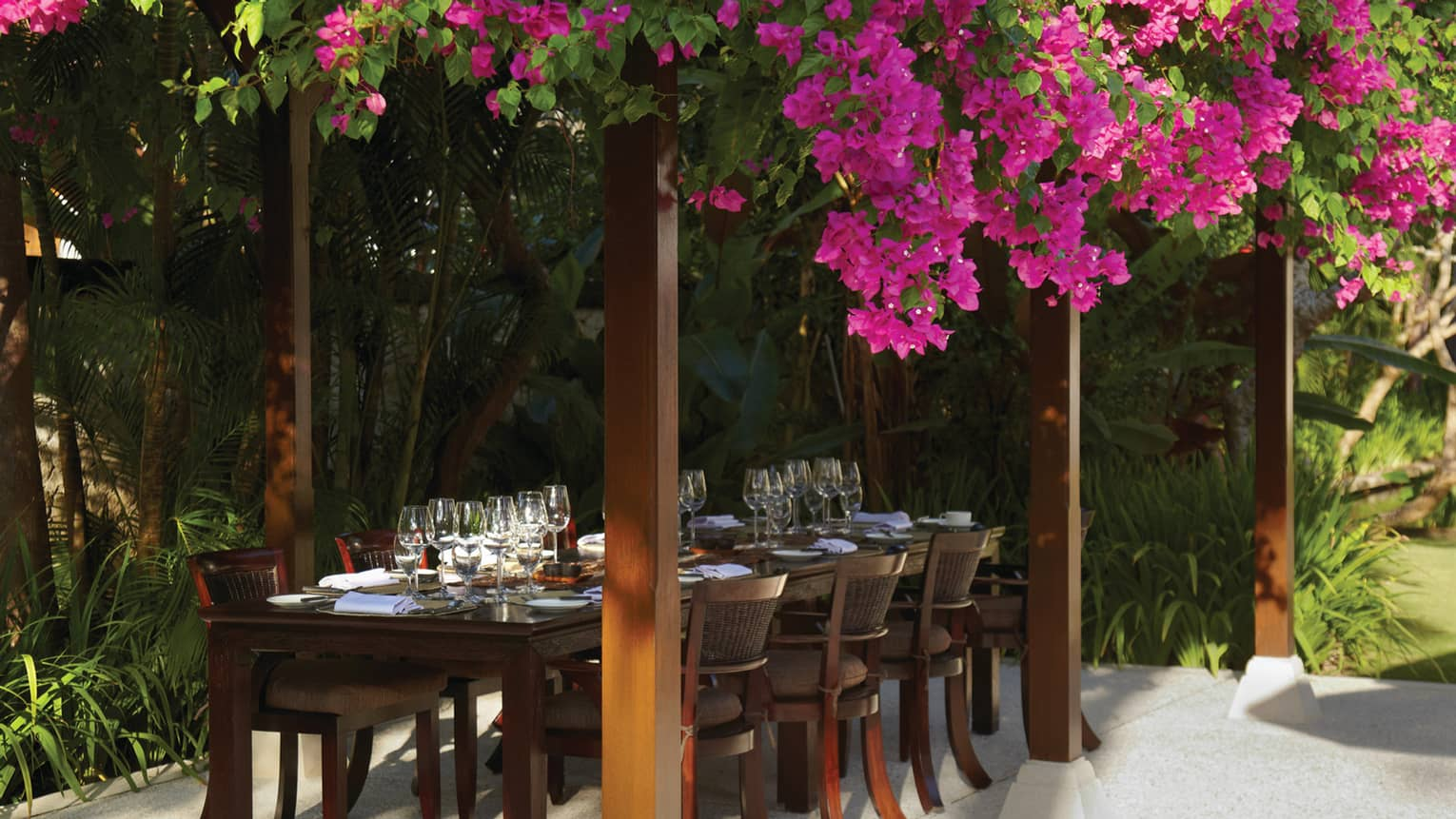 Purple flowers draped over pergola and large outdoor dining table