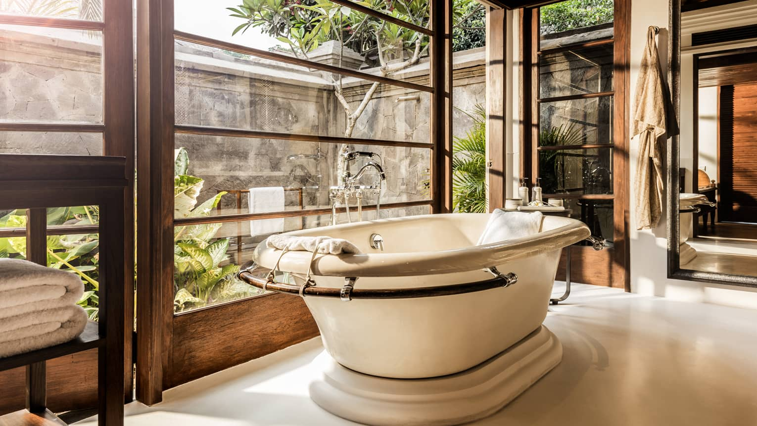 Free-standing bath tub with folded white towels, bathrobe hanging above, large window to garden