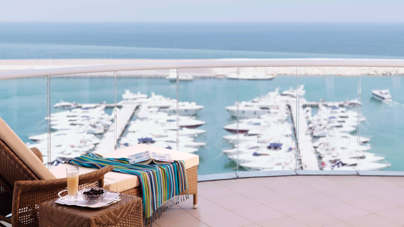 Colourful striped towel draped over wicker patio ottoman, book open and face down, rows of boats in harbour below