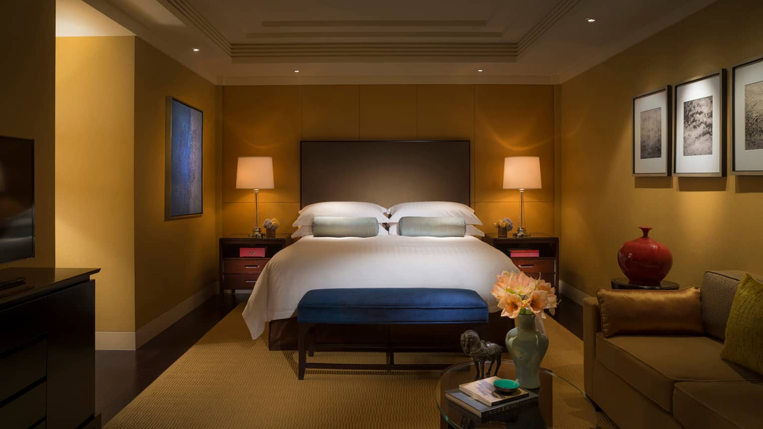 Dimly-lit hotel room bed with tall padded headboard, small blue bench at foot, small table with vase, horse statue