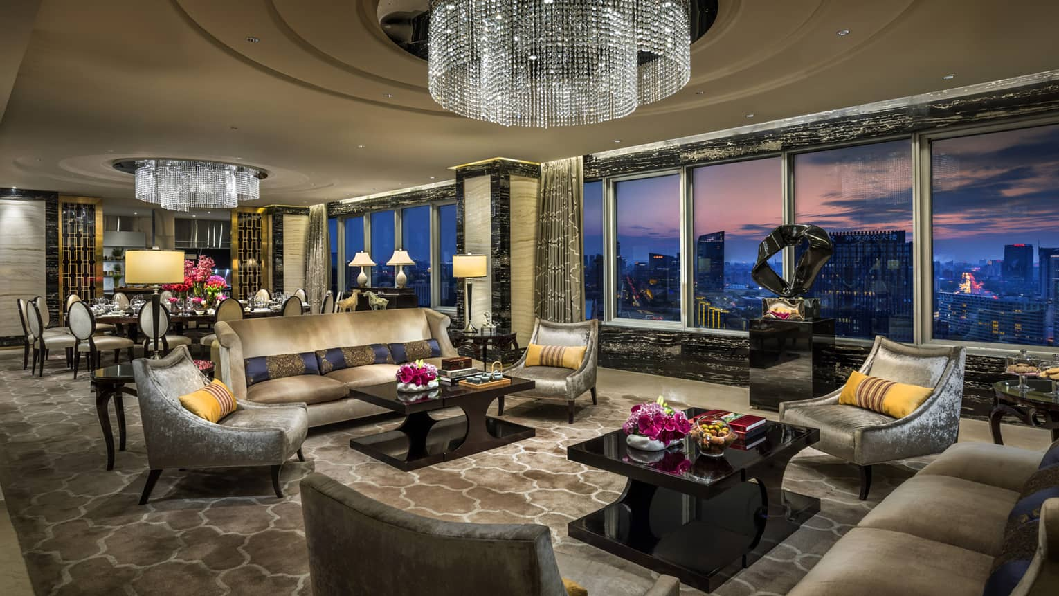 Imperial Suite luxurious living room with sofas, armchairs under large crystal chandeliers, floor-to-ceiling windows, sunset views
