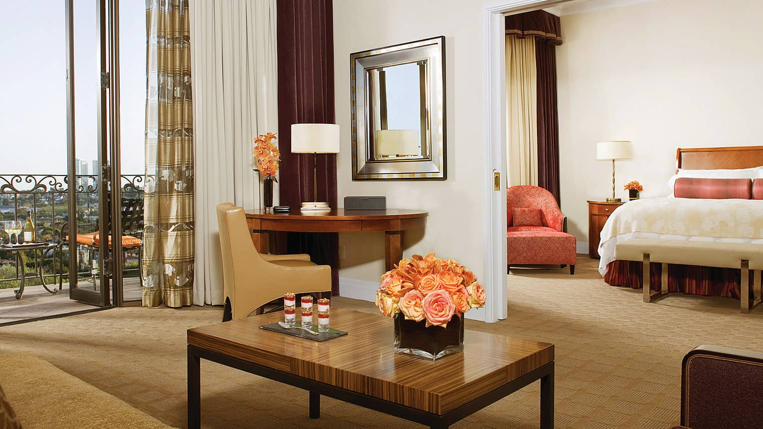 Deluxe Beverly Suite seating area, desk by large bay windows, balcony, bedroom door