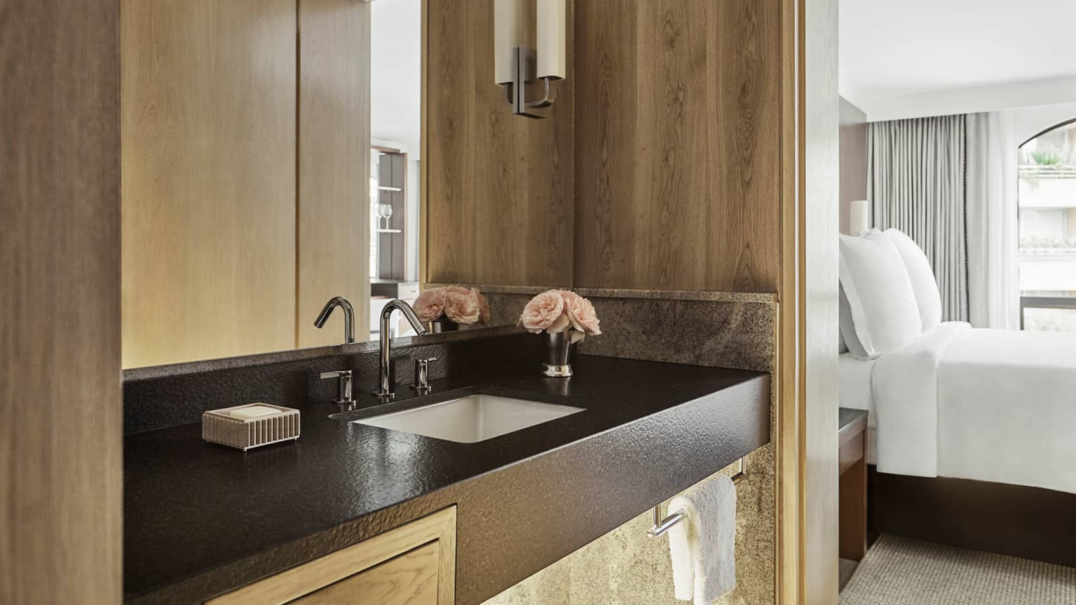 Close-up of bathroom vanity with black counter, sink, wood walls, bedroom visible to side