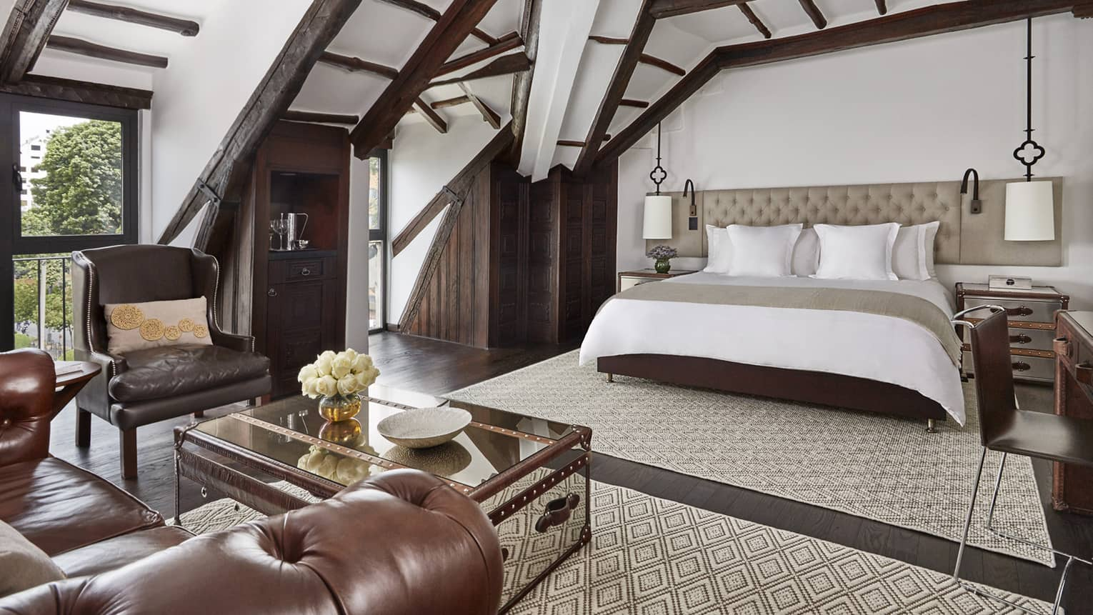 Sloped beam loft ceiling over hotel bed with padded headboard, brown leather armchair, table with flowers