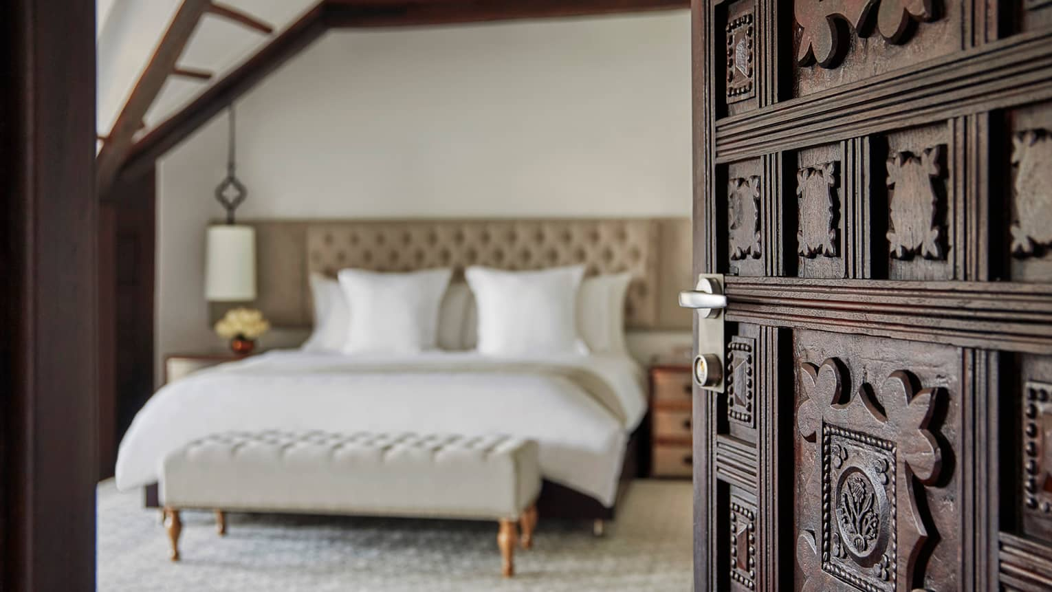 Premier Room close-up of decorative wood carved door opening to bedroom, bed with white linens, padded headboard