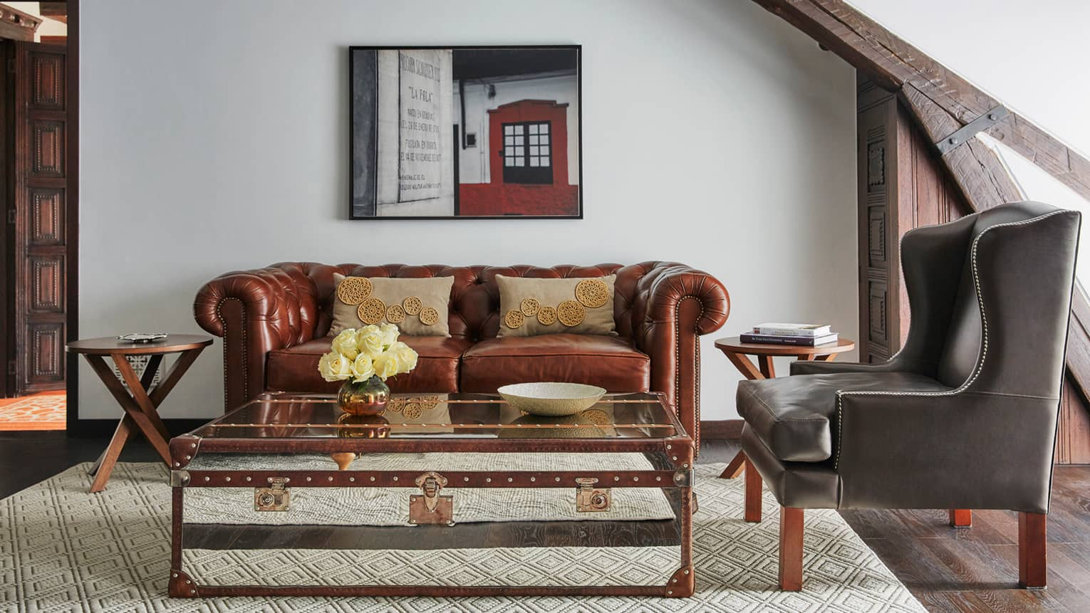 Trunk-style coffee table in front of period-style brown leather sofa, modern black armchair, oil painting