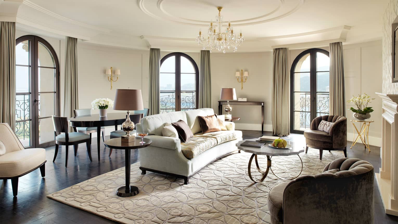 Circular living room in corner turret, French balcony doors, white sofa and area rug, plush chairs