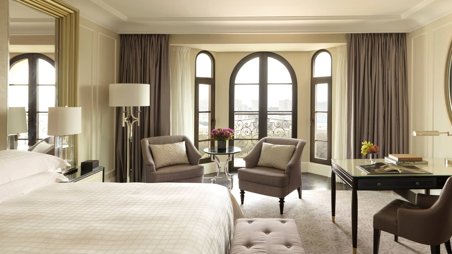 Sunny Deluxe Caspian Room hotel room with arched French doors, two armchairs, desk, bed