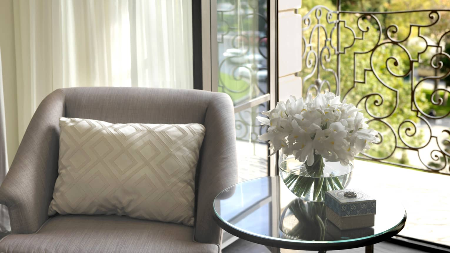 Close up of grey armchair with white accent pillow, glass table and vase with white flowers in sunny window