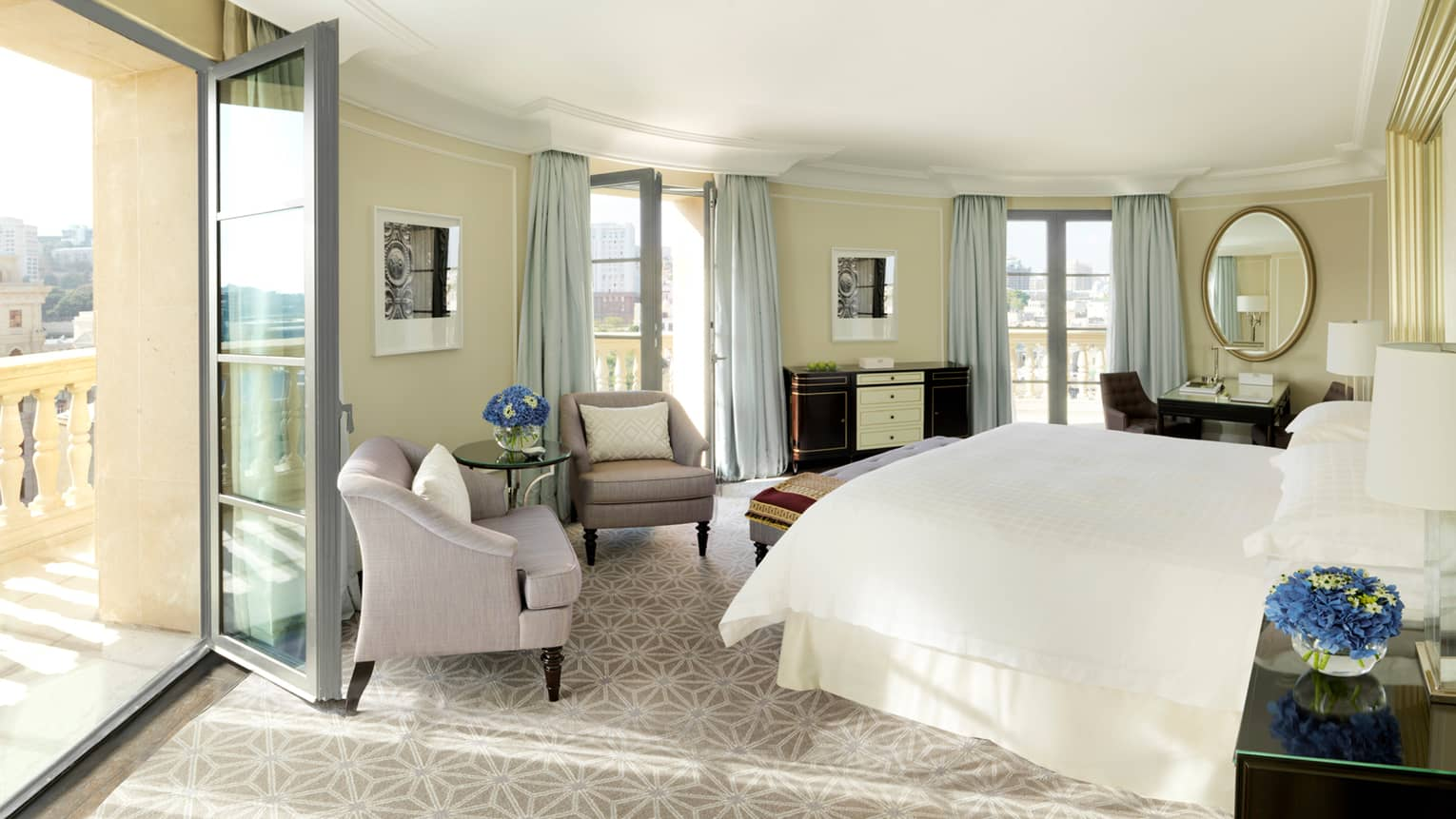 Sun streams in from open balcony door to curved hotel room with bed, plush armchairs, mirrors