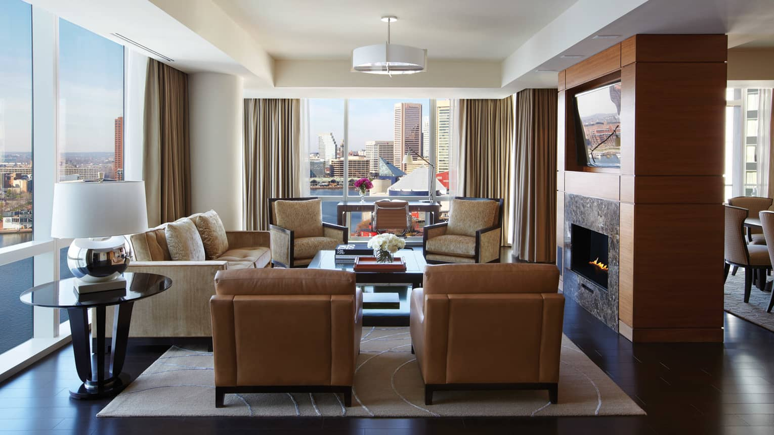 Serene Suite brown leather armchairs, sofa, chairs around gas fireplace, corner windows