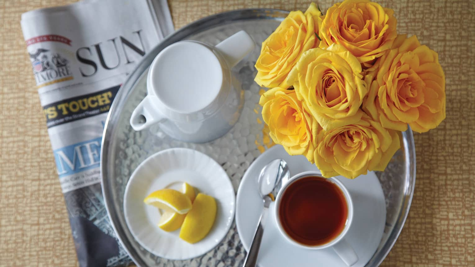 Aerial view of round silver tray with white teapot, tea in mug, yellow roses, newspapers