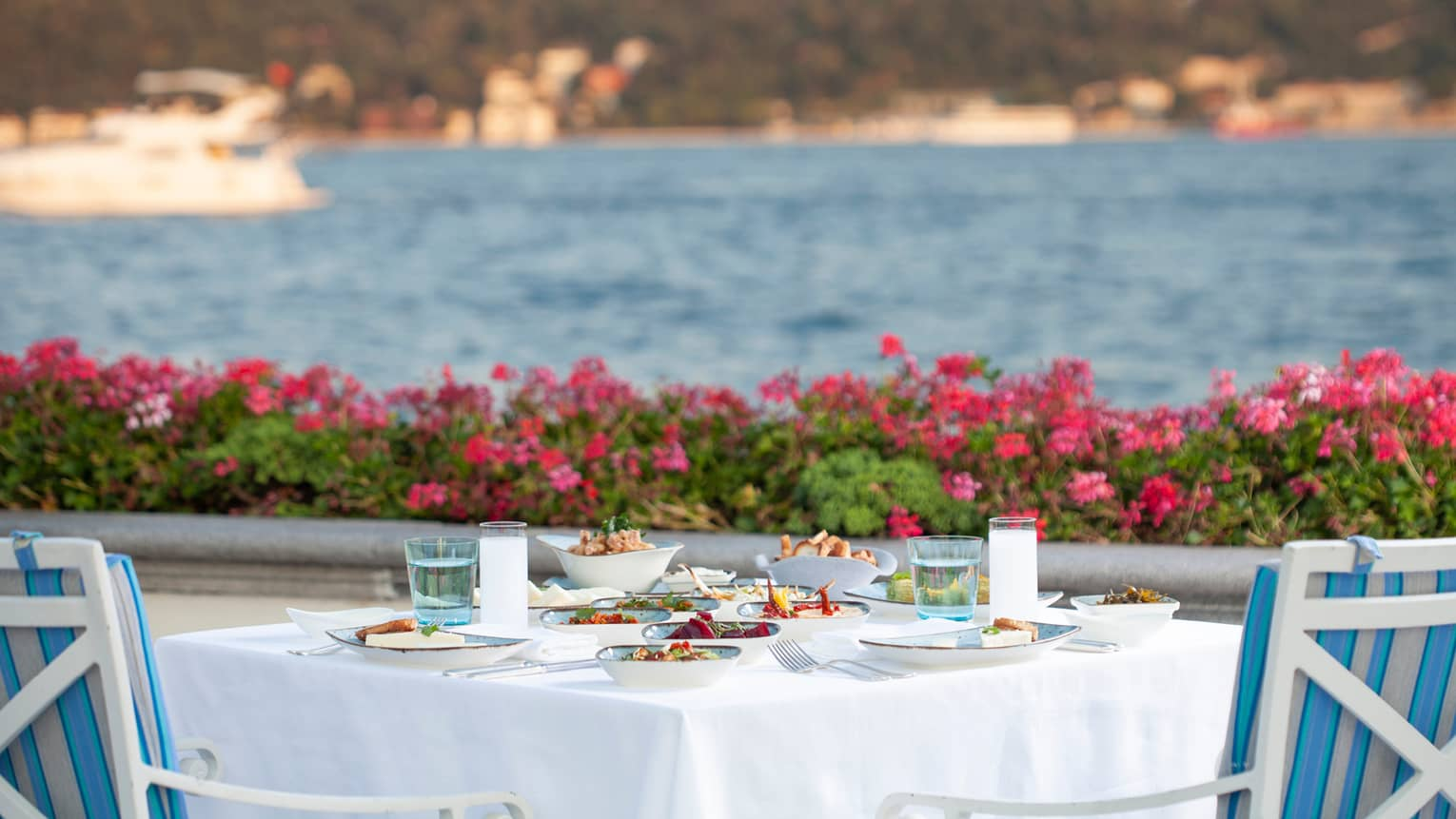 A meal is set on a square table with white tablecloth, two blue cushioned chairs, looking out to sea