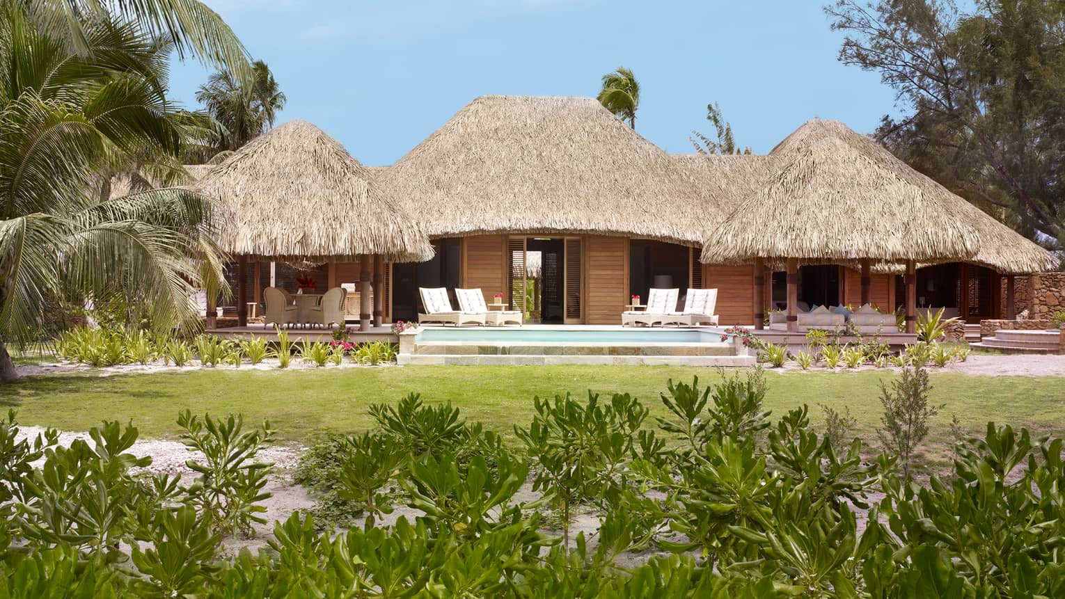 Outdoor view of beachfront bungalow with thatched roof, large patio and lounge chairs, green lawn