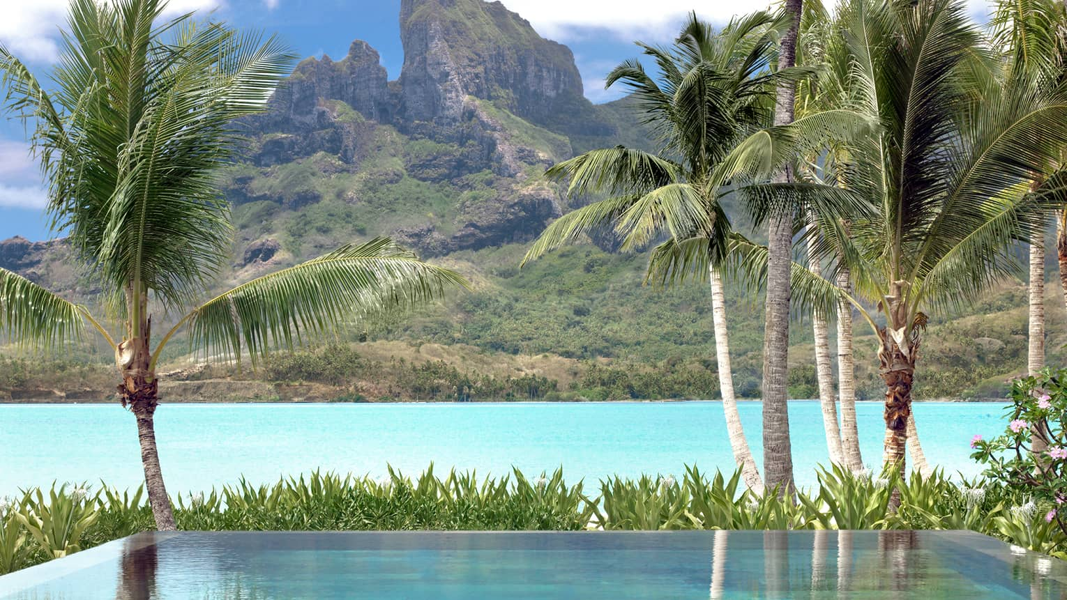 Otemanu beach plunge pool and palm trees overlooking lagoons, mountains