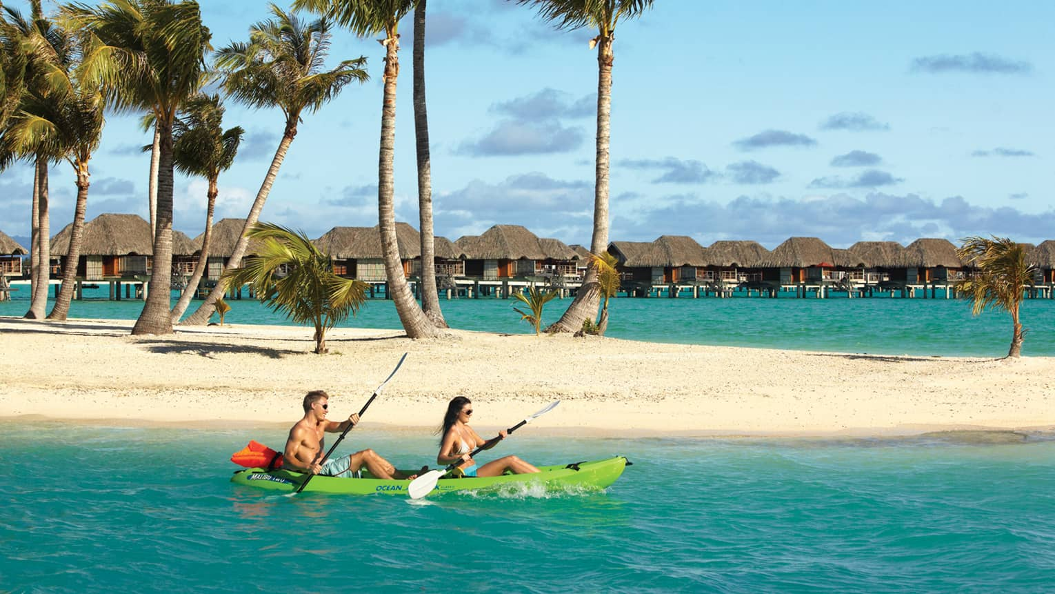 Couple kayaks past white sand motu and palm trees, underwater bungalows in background