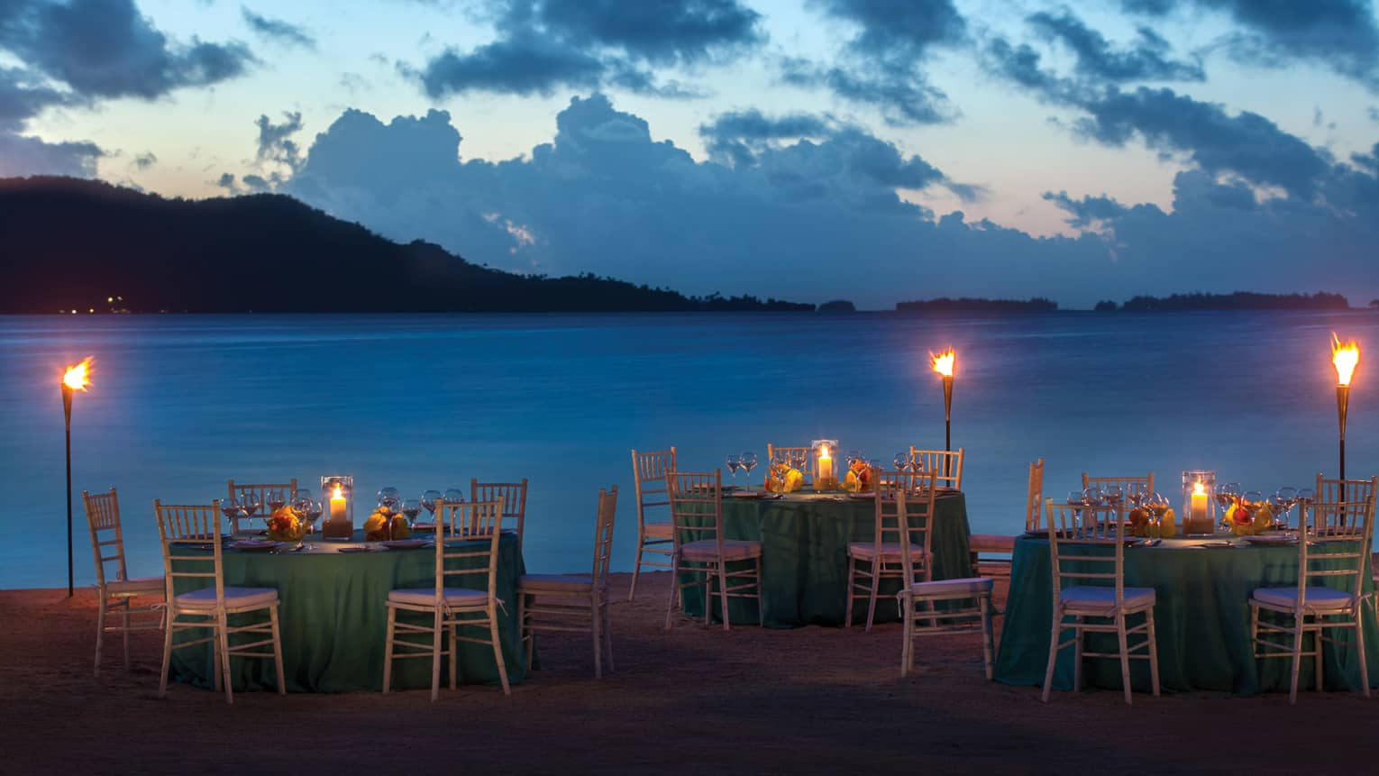 Fare Hoa Beach at dusk with candle-lit dining tables and torches