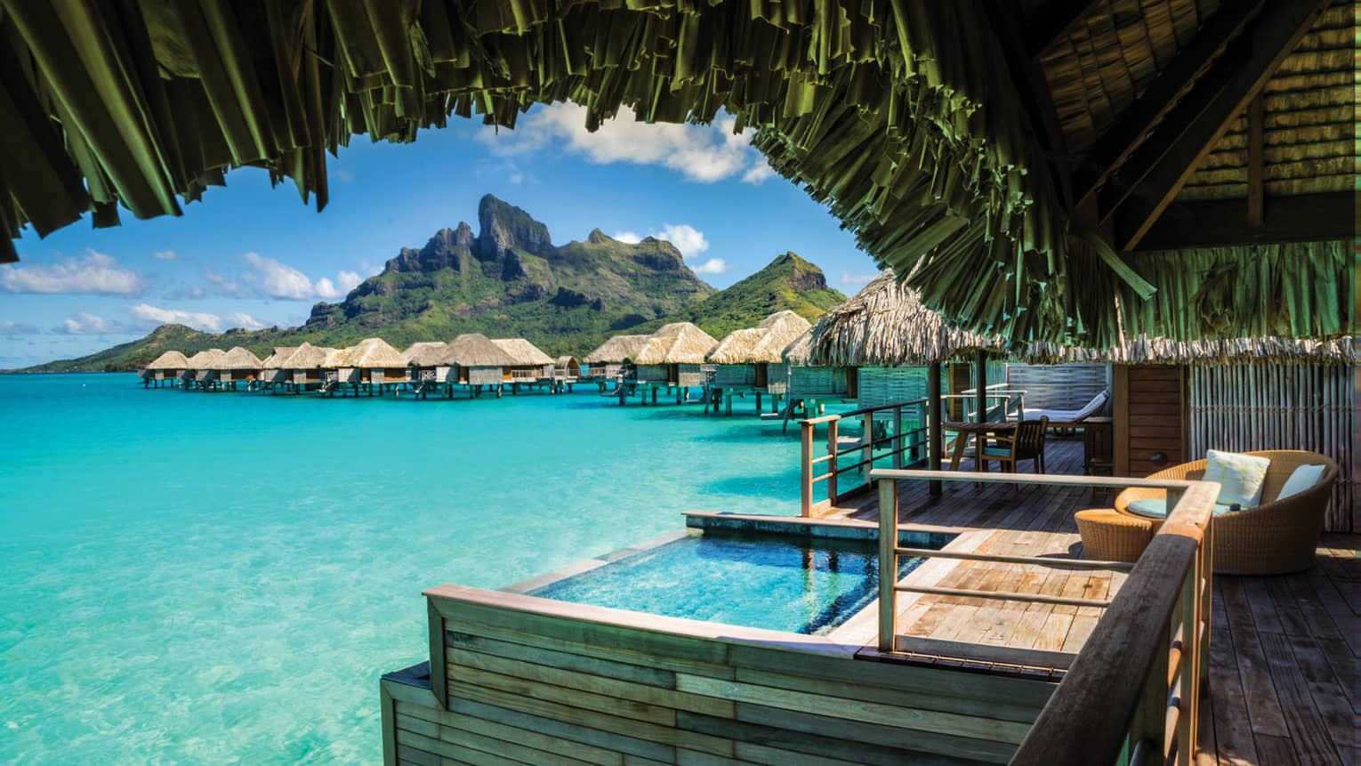View from under thatched roof of Poerava Overwater Bungalow Suite with plunge pool over lagoon