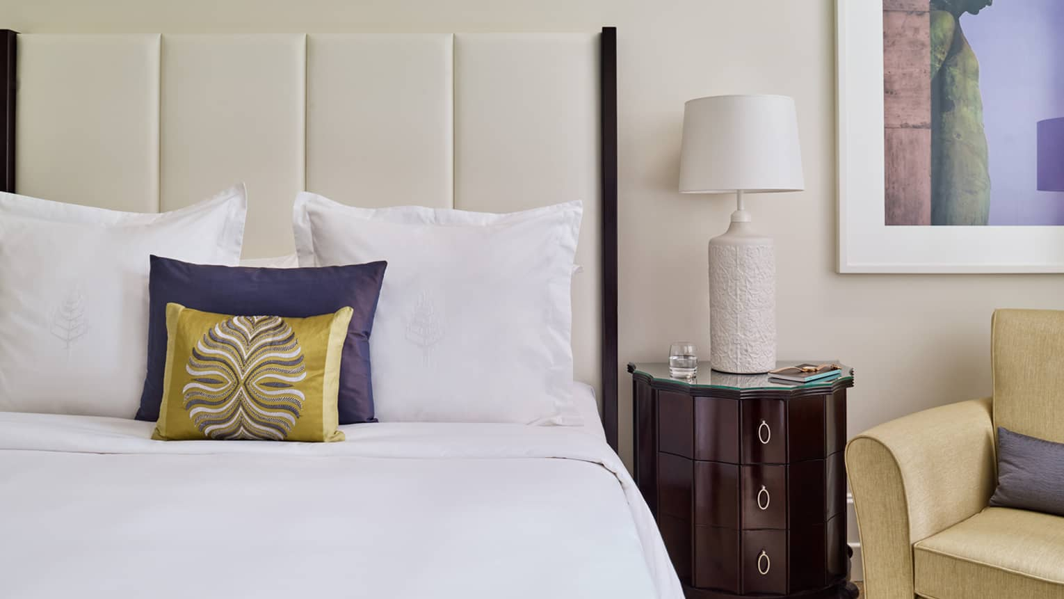 Close-up of Superior Room bed with white padded headboard, blue and gold accent pillows, lamp