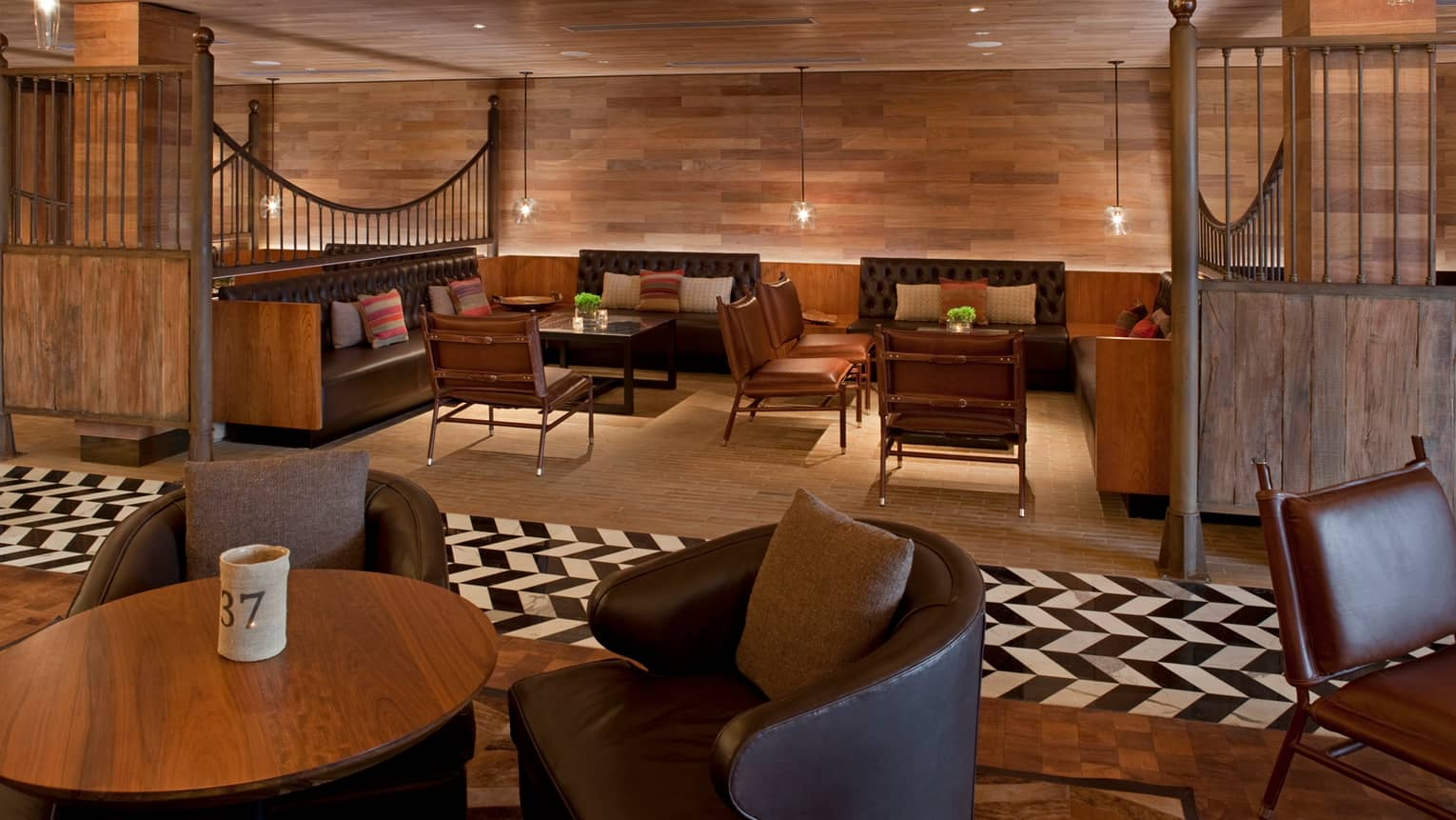 Pony Line lounge with rich brown wood flooring and walls over tables with stools, leather chairs, glass lamps
