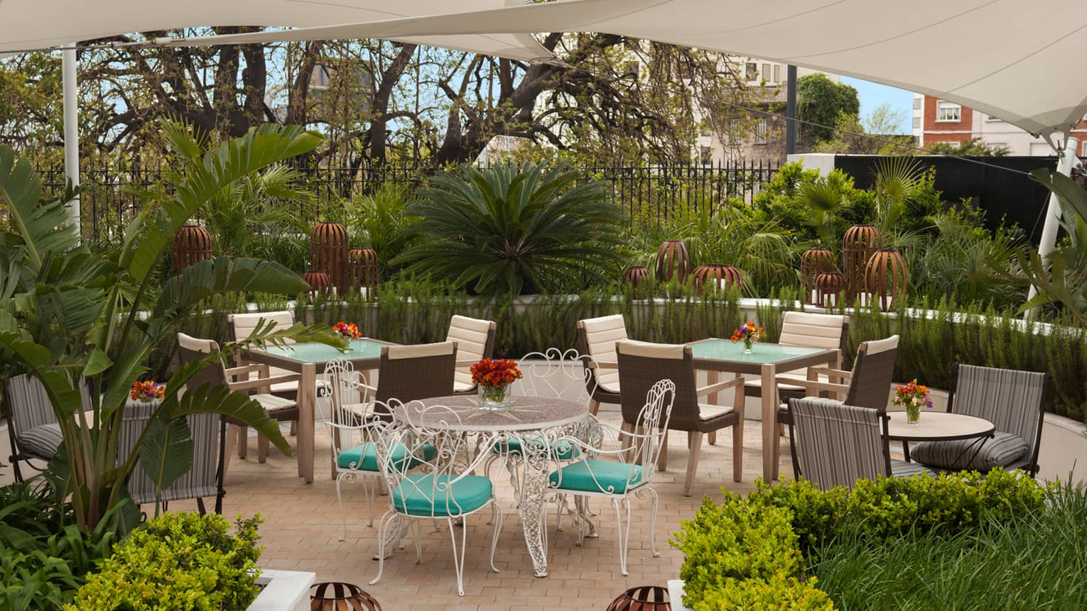 Outdoor patio dining tables with white chairs, teal cushions, surrounded by tropical gardens