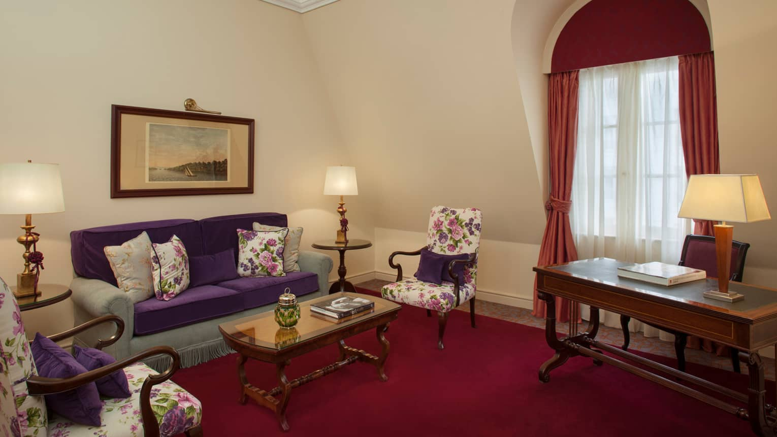 La Mansión Diplomatic Executive Suite deep red carpet, blue-and-purple sofa, floral armchairs