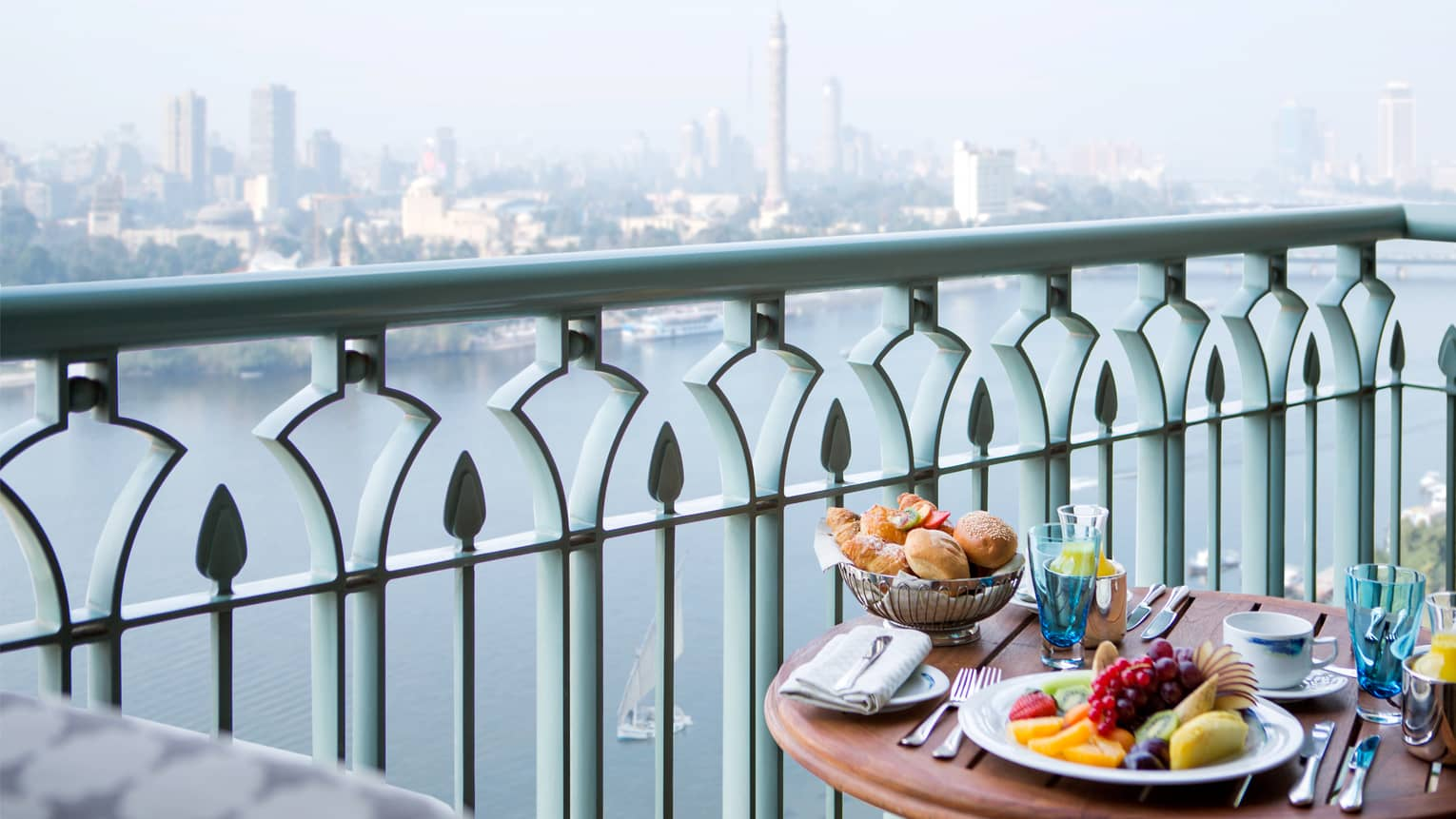 Close-up of balcony table with plate of fresh fruit, bread and orange juice, river and city view below