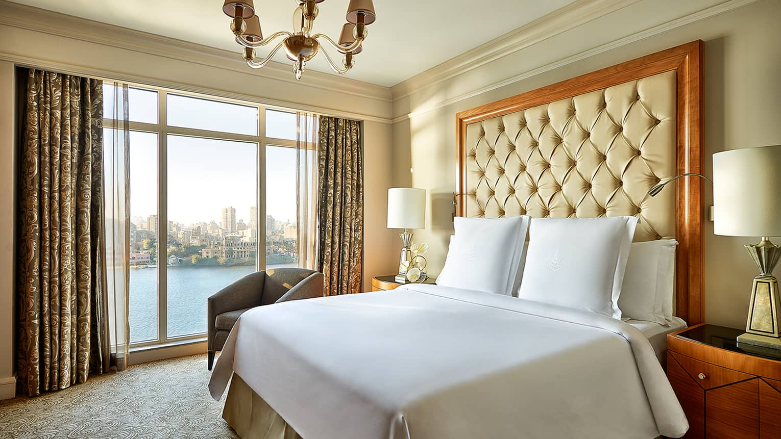 Diplomatic Suite bed with white bedspread, pillows and tall beige leather headboard beside tall window with river view