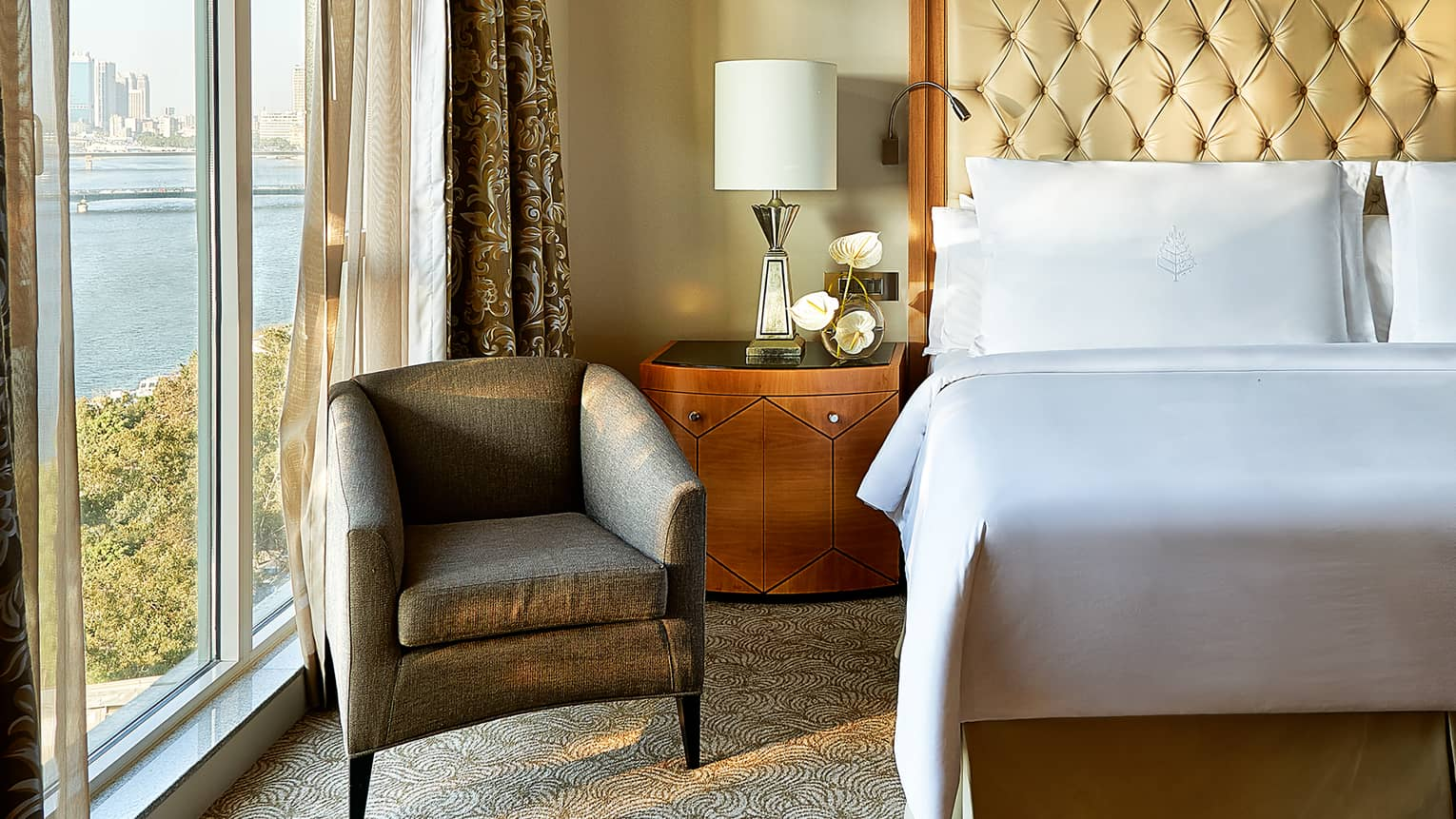 Royal Suite close-up of white pillows and tall leather headboard, wooden side table with lamp and white orchids