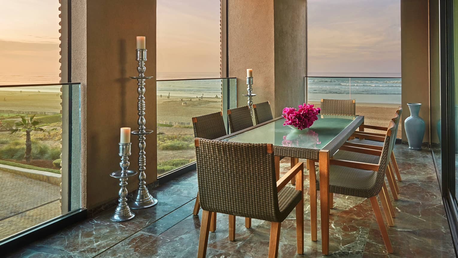 Balcony dining table with wicker chairs, fresh pink flowers, tall silver pillar candles, ocean views