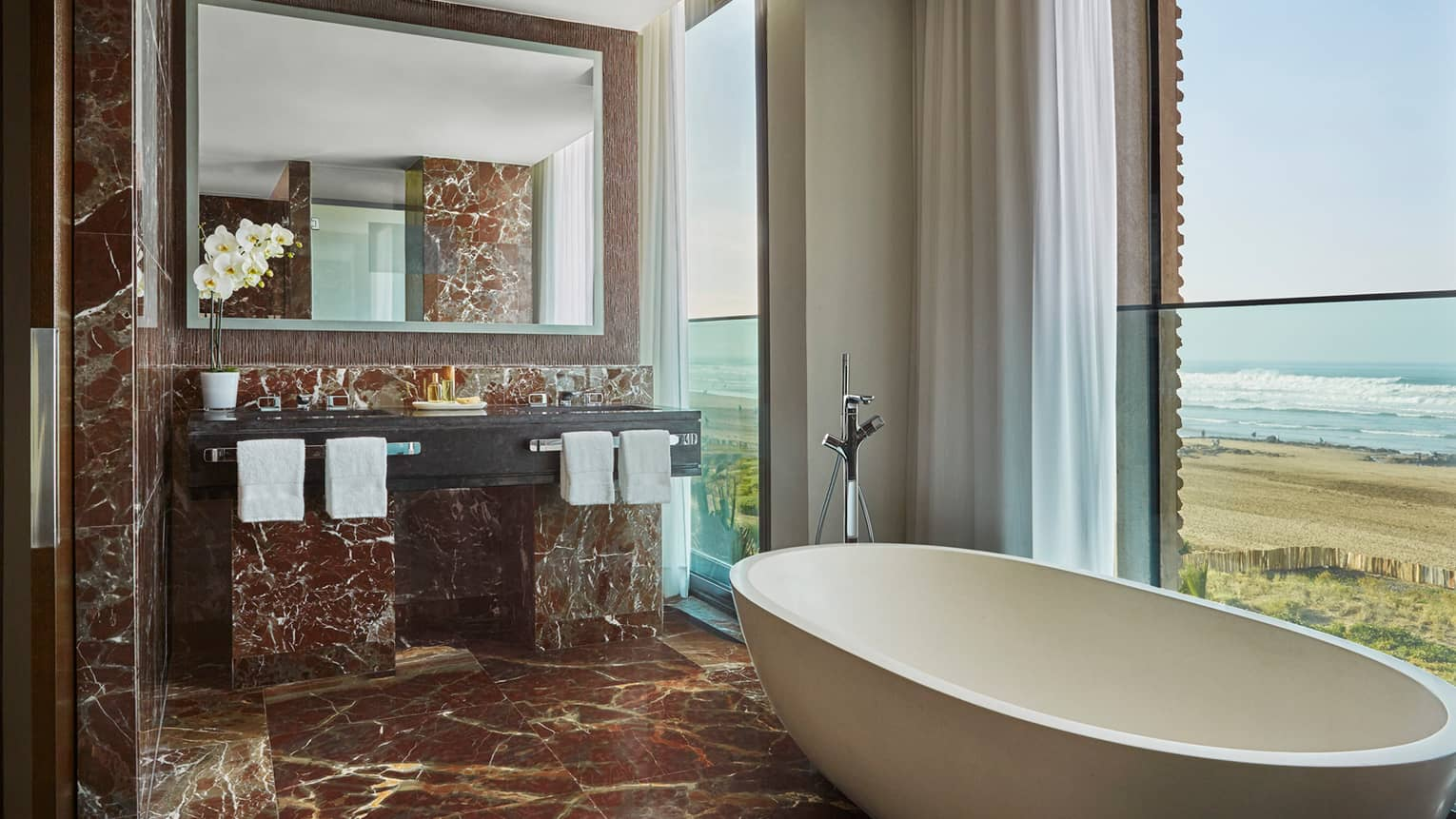 Signature Suite bathroom with deep soaker tub in front of window with ocean view, brown marble floor, wall