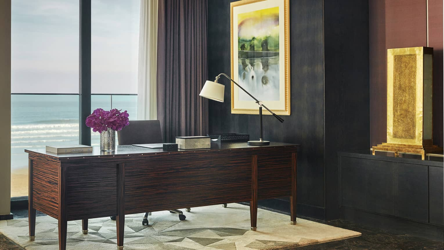 Royal Suite Ocean View office with large executive desk, lamp and purple flowers