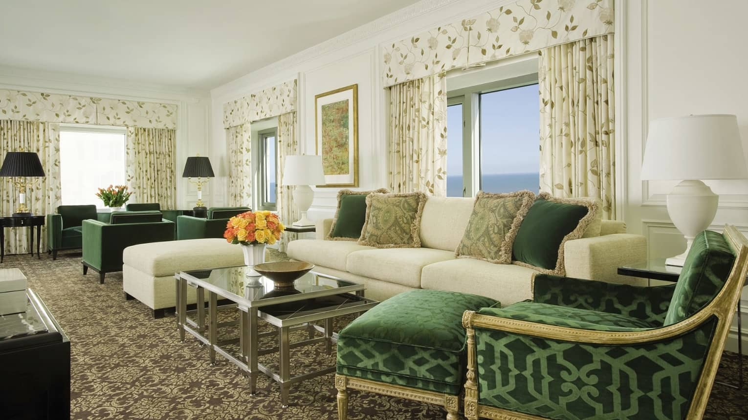 Presidential Suite living room with white sofa, ottoman, green accent pillows, elegant green chaise, green chairs, white curtains