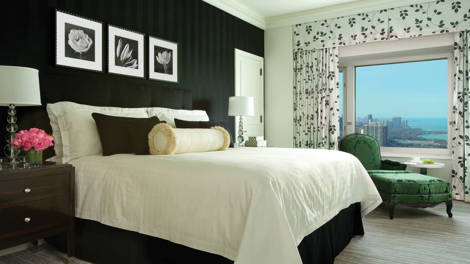 Presidential Suite bed with white linens, black accent pillows, black wallpaper, green silk floral chaise, black-and-white drapes
